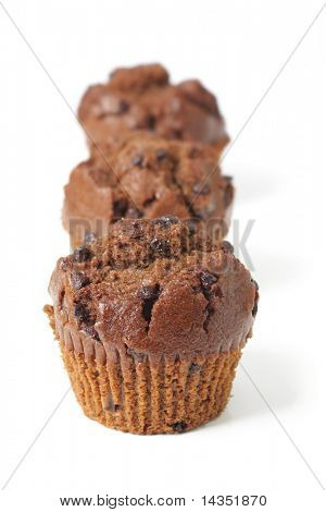 Three fresh-baked chocolate-chip muffins in a row, isolated on white.  Shallow DOF, and natural shadow.