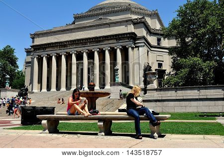New York City - September 2 2009: Two students reading on a bench in front of the Library of Columbia University