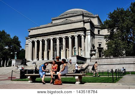 New York City - September 2 2009: Three women seated on stone bench in front of the Library of Columbia University