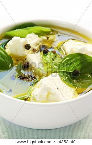 Goat's cheese (feta) flavored with basil leaves and peppercorns in virgin olive oil.
