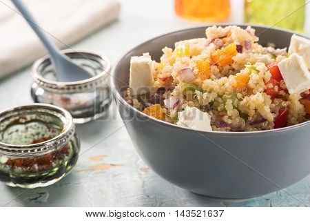 Close up of colorful quinoa salad with goat cheese on blue vintage wooden table