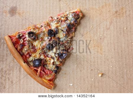 Last lonely slice of pizza, in pizza box.  Capricciosa, with black olives, ham, mushrooms,  and mozzarella.