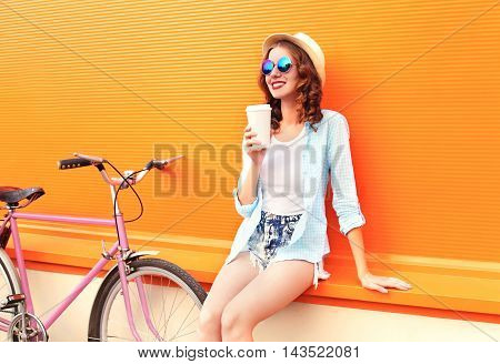 Fashion Pretty Woman Drinks Coffee Of Cup Near Retro Vintage Pink Bicycle Over Colorful Orange Backg