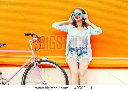 Fashion Pretty Woman Listens To Music In Headphones Near Retro Pink Bicycle Over Colorful Orange Bac