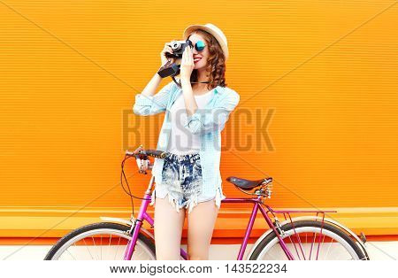 Fashion Pretty Woman With Retro Camera And Bicycle Over Colorful Orange Background In Profile