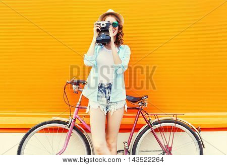 Fashion Pretty Woman With Retro Camera And Bicycle Over Colorful Orange Background
