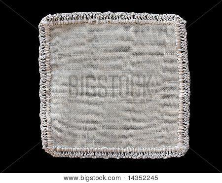 Edged beige fabric swatch, on black background.