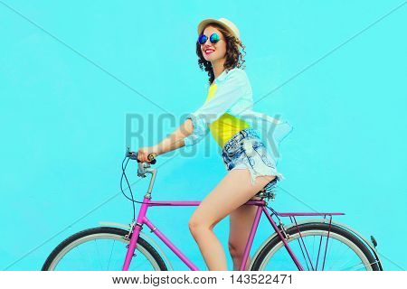 Happy Pretty Young Woman Rides A Bicycle Over Colorful Blue Background In Profile