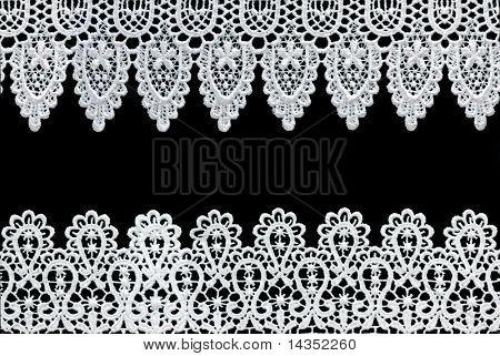 Encaje blanco forma una frontera delicada sobre fondo negro.