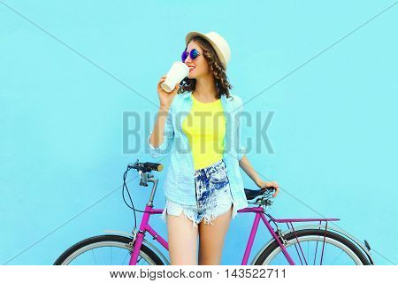 Pretty Smiling Woman With Coffee Cup And Bicycle Over Colorful Blue Background In Profile