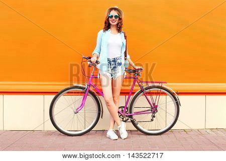 Pretty Smiling Woman With Bicycle Over Colorful Orange Background