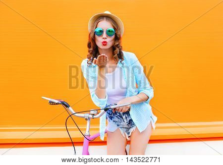 Pretty Woman Sends Air Kiss On Bicycle Over Colorful Orange Background