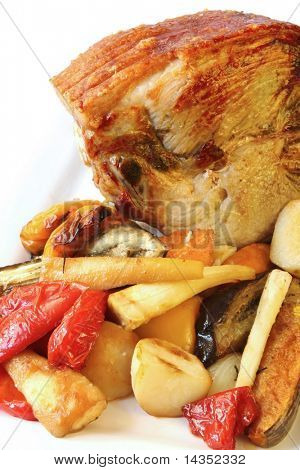 Roast pork with vegetables.  Leg of pork with crackling, surrounded by roasted potatoes, bell peppers, pumpkin, sweet potato, parsnip, onions and eggplant.