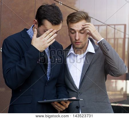 Two Businessman Looking At Tablet. Failure In Work.
