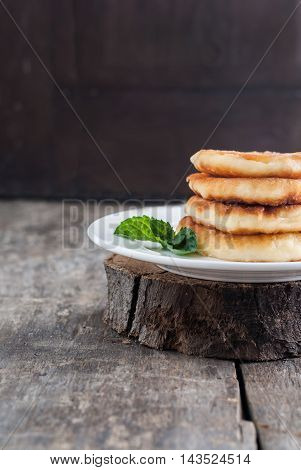 Stack Of Cheesecakes On A White Plate And A Dark Wooden Background