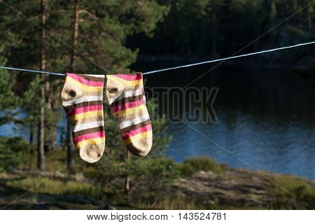 Bright socks drying after washing on the clotheline outdoors