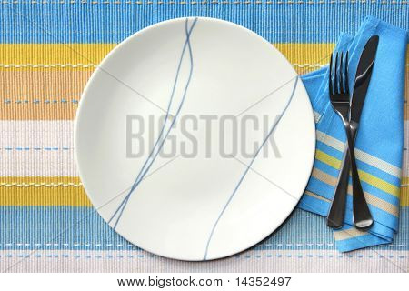Place setting in tones of blue,yellow, tan and white.