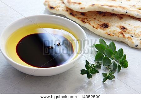 Oil and vinegar - small bowl of olive oil and balsamic vinegar, with dipping bread and fresh herbs.