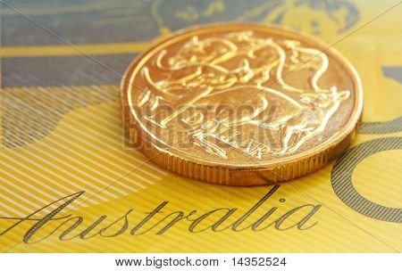Australian one dollar coin on a fifty dollar note.  Close-up view, with shallow depth of field.
