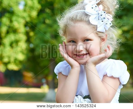 child girl portrait touch face closeup, posing in white gown, happy childhood concept, summer season in city park
