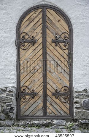 Old wooden door with wrought iron and bolts.