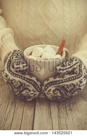 Hands in knitted mittens holding hot chocolate, rustic wood background, toned