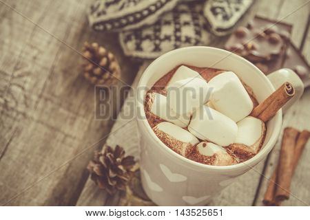Hot chocolate with marshmallow and cinnamon, rustic wood background, toned