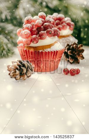 Christmas cupcake with red berries, rustic wood background, toned, snow