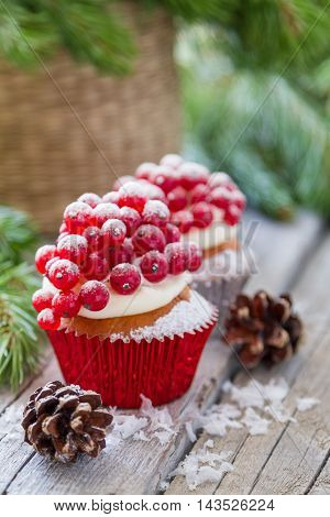 Christmas cupcake with red berries, rustic wood background