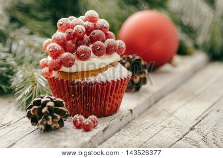 Christmas cupcake with red berries, rustic wood background, toned