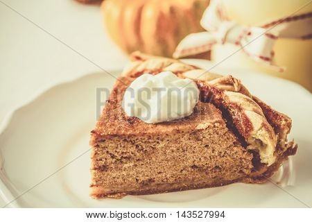 Pumpkin pie on white wood background toned