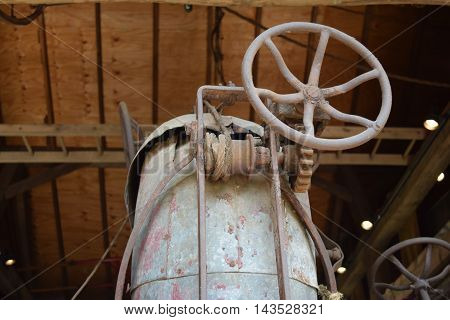 a old antique hand crank winch with a iron wheel.