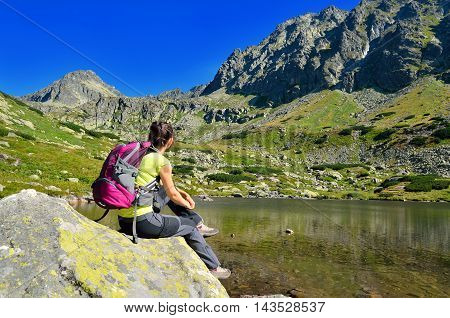 Tourist in the mountains. Young woman on the lake admiring mountain peaks.