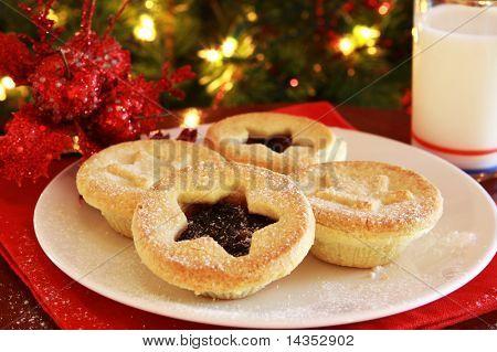 Papai Noel trata - prato de Natal mince tortas e copo de leite, com árvore de Natal por trás.