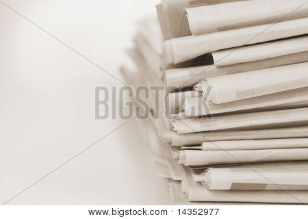 Newspaper stack in sepia tone, with soft-focus and shallow depth of field.  Lots of copy-space.