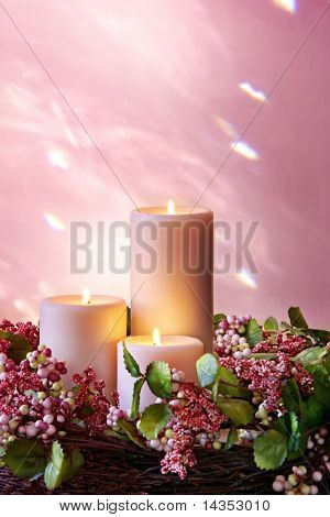Christmas candles in a pastel floral wreath.  Background is natural light reflected from bevelled glass.