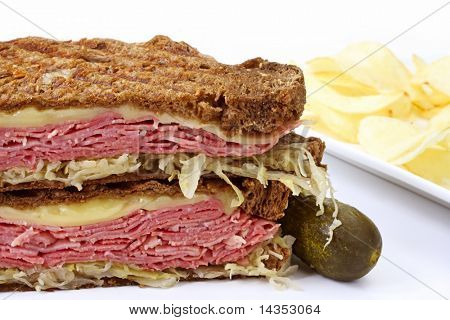 Traditional Reuben sandwich, with grilled rye bread, corned beef, melted Swiss cheese and sauerkraut.  Served with a pickle and potato chips.