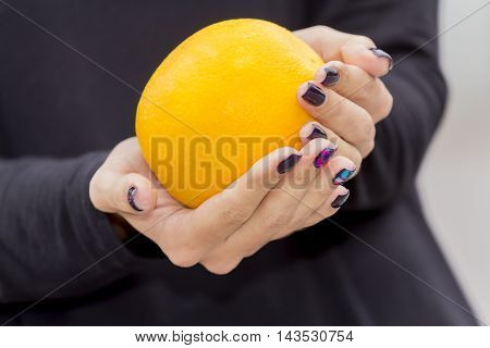 Hands girl with fashionable manicure keep oranges on the street.
