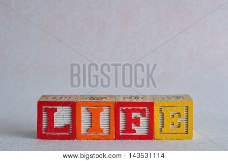 The word life spelled with colorful blocks isolated on a white background