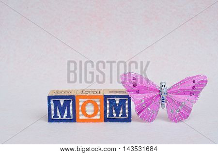 Mom spelled with block displayed with a silk butterfly