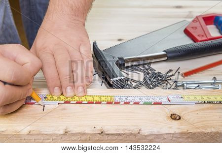 Close-up image with a carpenter measuring a plank of wood and a bunch of woodworking tools in the background.
