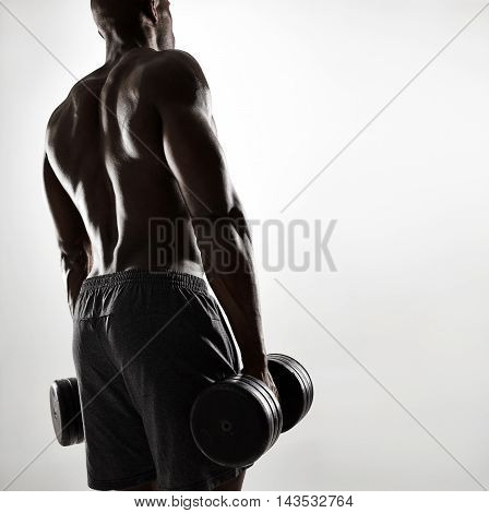 Muscular Young African Man Exercising With Dumbbells