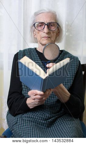 Grandma Reading A Book Through Magnifying Glass