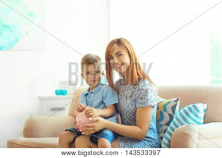 Savings concept. Mother and little boy sitting on sofa with piggy bank