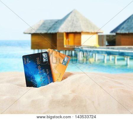 Credit cards on beach. Blurred water villa resort background.