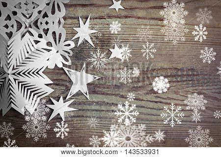 Winter background with hand-made paper snowflakes on wooden background. Snow effect