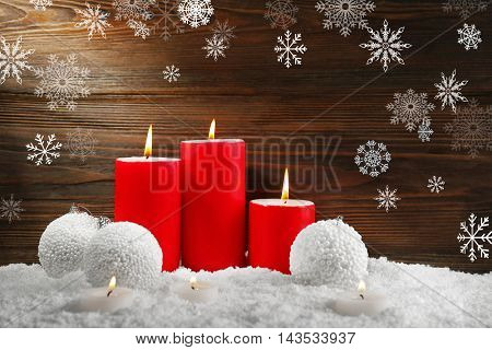 White baubles with candles in a snow over wooden background, still life. Snow effect