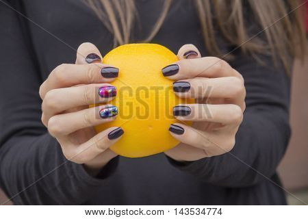 Bright, fresh orange in the hands of the girl with the fashionable manicure