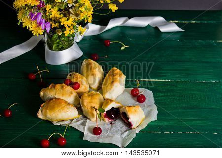 Traditional Russian cuisine: cakes with sour cherries. Still life with cakes and a vase with flowers on a green wooden table in rustic style.