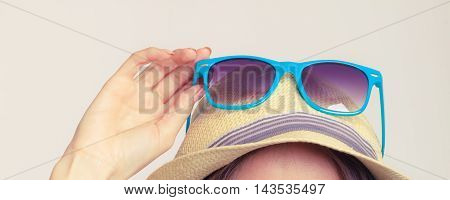 Summer girl holding sunglasses. Happy protected tourist enjoyed vacation.